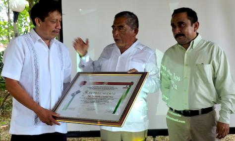 Bernardo Caamal recibe un reconocimiento de manos de Sebastián Pool Estrella y de Jesús Aguilar Be, en Felipe Carrillo Puerto